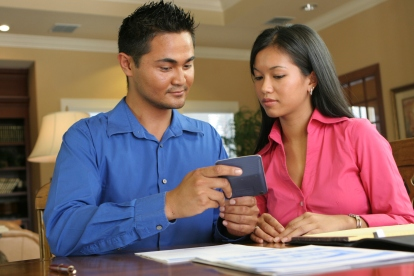 Close-up of a young couple looking at a calculator